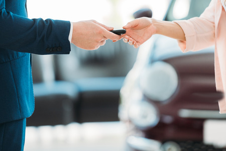 Cropped image of sales manager giving car key to customer after purchase