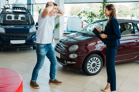 Sales manager showing to happy and surprised customer a car he won
