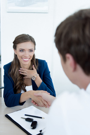 customer and smiling sales manager shaking hands after purchase