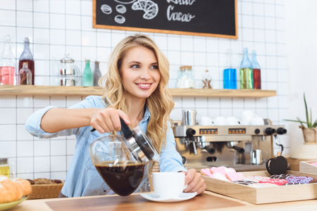 beautiful smiling young barista pouring coffee and looking away in cafe