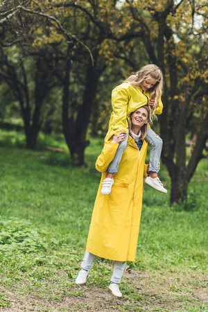 happy mother and daughter standing in yellow raincoats at countryside