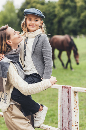 happy stylish mother and daughter standing at paddock with horse Reklamní fotografie