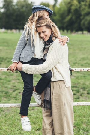 stylish mother and daughter in autumn outfit sitting on fence at countryside