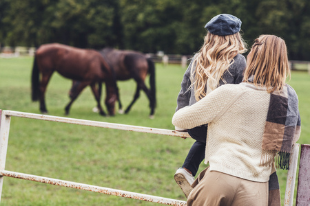 rear view of mother and daughter standing at paddock with horses Banco de Imagens - 102362053