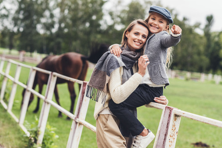 happy stylish mother and daughter standing at paddock with horse Foto de archivo - 102357702