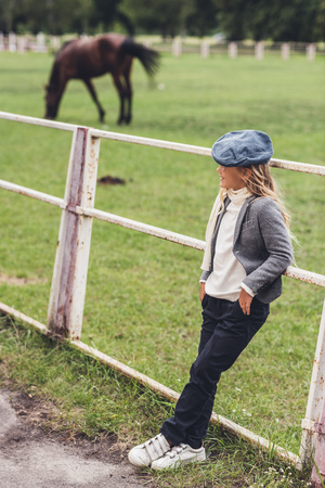 adorable blonde child at paddock with horse behind