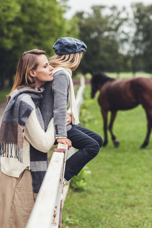 stylish mother and daughter standing at paddock with horse