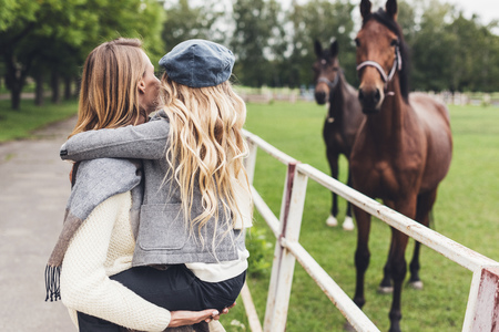happy stylish mother and daughter standing at paddock with horses Stock Photo