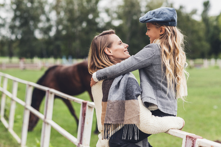 happy stylish mother and daughter standing at paddock with horse