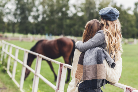 back view of stylish mother and daughter standing at paddock with horse Stock Photo