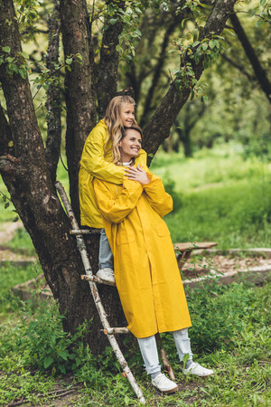 smiling mother and daughter standing in yellow raincoats at countryside