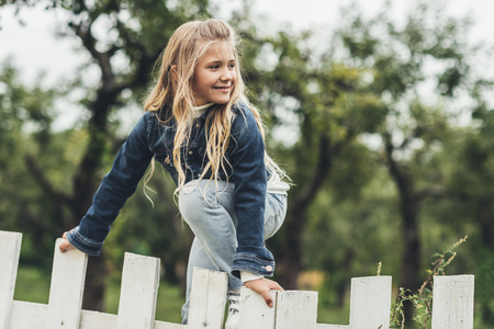 spring blonde child climbing over the fence at countryside