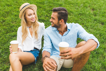 smiling coupe with coffee to go in hands looking at each other while resting on green lawn 写真素材