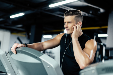 young sportsman training on treadmill and listening music in sport center Zdjęcie Seryjne