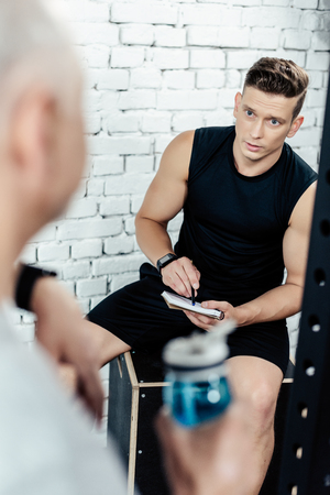 young trainer talking with senior sportsman in sport center Stock Photo