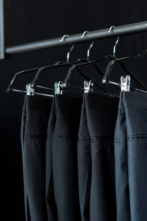 close-up view of fashionable suit pants on hangers in boutique