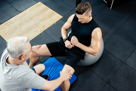 young sportsman doing abs on fitness ball in gym with senior trainer