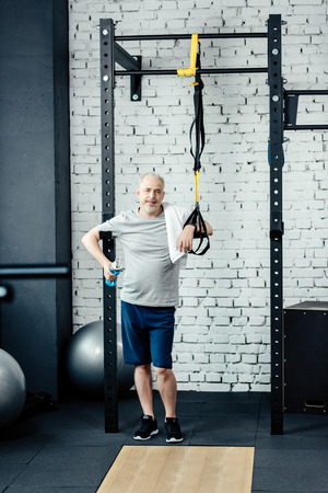 senior sportsman resting after training with trx in gym