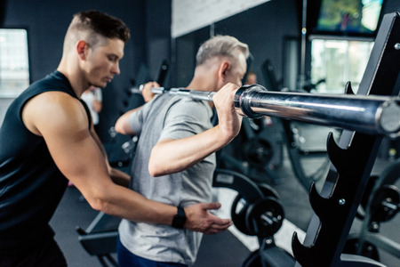 senior sportsman lifting barbell with trainer in gym    写真素材
