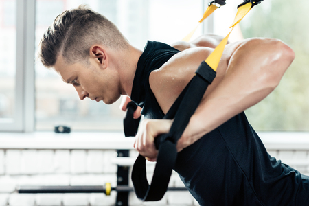 young muscular sportsman training with trx resistance bands in gym   Stockfoto