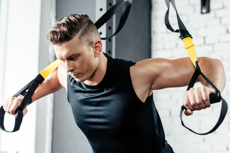young muscular sportsman training with trx resistance bands in gym   Zdjęcie Seryjne