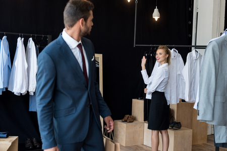 young businessman looking at young woman waving hand in boutique 写真素材 - 102362745