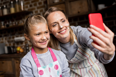 portrait of smiling mother and little daughter with flour on faces taking selfie together