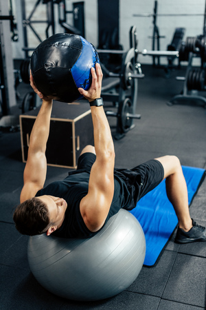 young sportsman training on fitness ball with medicine ball in gym