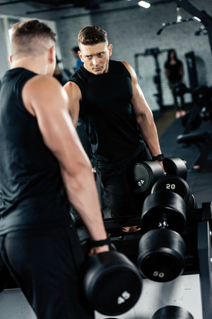 young muscular sportsman training with dumbbells in gym Reklamní fotografie - 102362781