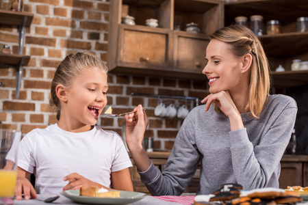 portrait of mother feeding preteen girl during lunch at home