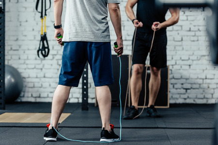 cropped view of sportsmen training with skipping rope in gym