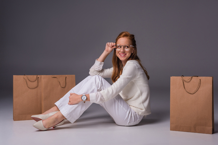 smiling fashionable girl in white clothes with shopping bags, on grey