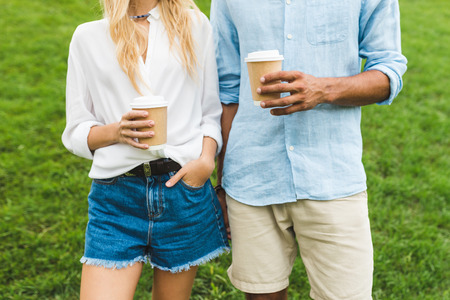 partial view of man and woman holding coffee to go in hands
