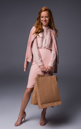 smiling elegant lady in pink clothes with shopping bags, on grey  Stockfoto