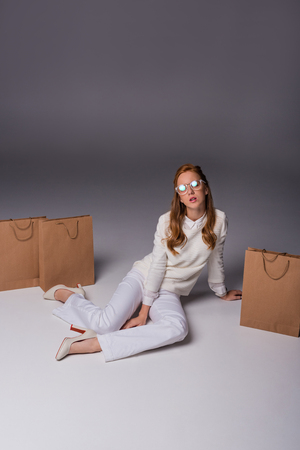 attractive elegant girl in white clothes with shopping bags, on grey