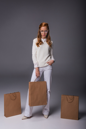 attractive fashionable girl in white clothes with shopping bags, on grey