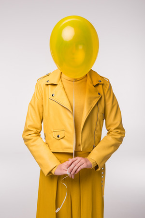 fashionable girl in yellow leather jacket with balloon, isolated on grey