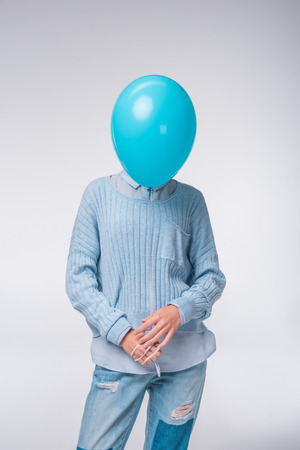 elegant girl in blue clothes holding balloon, isolated on grey