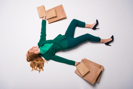 top view of excited stylish girl in green suit lying with shopping bags, isolated on grey, shopaholic concept