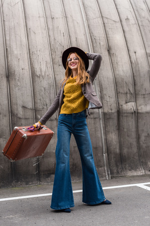 elegant stylish redhead girl in fedora hat holding vintage suitcase