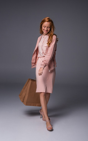 redhead fashionable girl in pink clothes holding shopping bags, on grey Stock Photo
