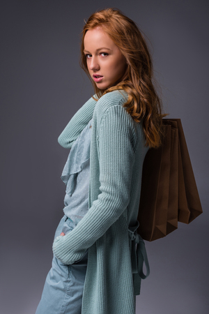 attractive elegant redhead girl in blue clothes with shopping bags, isolated on grey