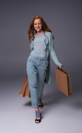 happy elegant redhead girl in blue clothes with shopping bags, on grey