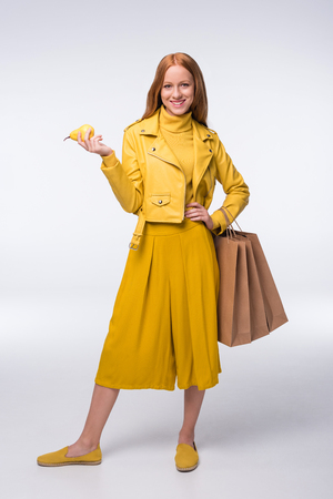 elegant redhead stylish girl in yellow clothes holding shopping bags and pear, isolated on grey