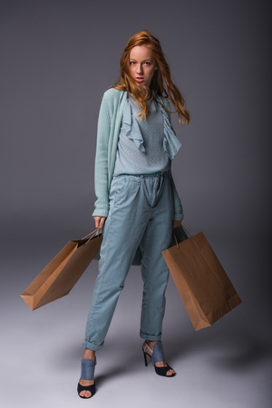 beautiful elegant girl in blue clothes with shopping bags, on grey