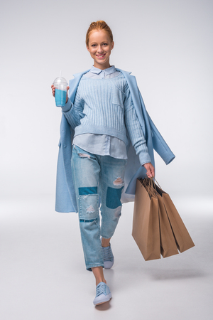 beautiful redhead stylish girl in blue autumn outfit holding shopping bags and blue drink, on grey