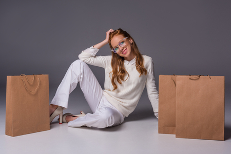 beautiful fashionable girl in eyeglasses and white clothes with shopping bags, on grey