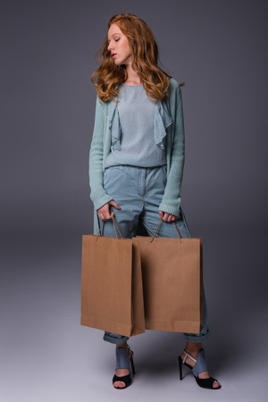 beautiful elegant redhead girl in blue clothes with shopping bags, on grey  Stockfoto