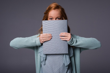 beautiful girl in blue clothes holding book, isolated on grey  Stock fotó