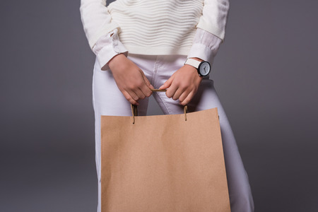cropped view of girl in stylish white clothes holding shopping bag, isolated on grey